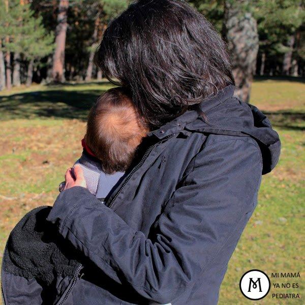 Madre porteando bebé. Uso de portabebés ergonómicos